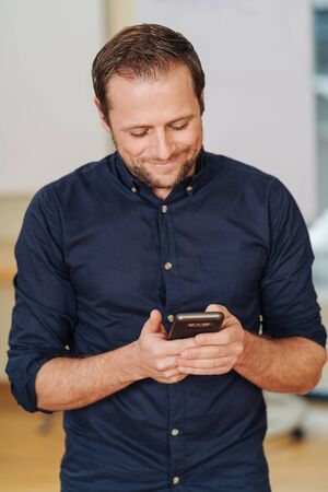 Cheerful man standing with mobile phone in office Stock Photo