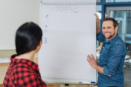 Happy smiling man giving a business presentation as he stands holding a flip chart listening to a woman ask questions in an over the shoulder view