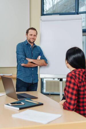 Young businesswoman interacting with a lecturer or colleague giving a business presentation as he stands alongside a flip chart in an office Stock Photo
