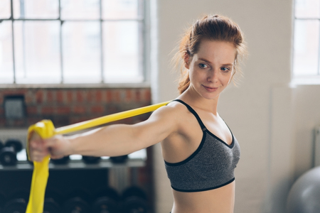 Young shapely woman doing exercises in a gym stretching out her arms using straps with a quiet smile of pleasure in a healthy lifestyle concept Stock Photo