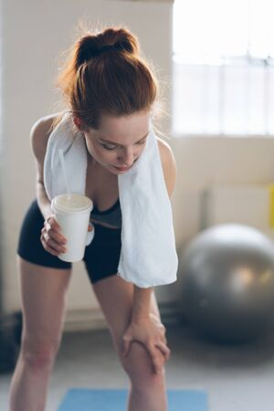 Fit young woman holding a disposable takeaway cup of coffee in a gym as she bends forwards on her knee relaxing after a workout
