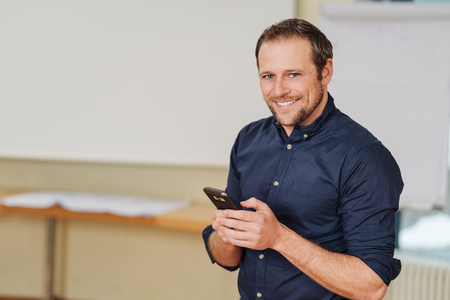 Portrait of cheerful man standing with mobile phone in office Stock Photo
