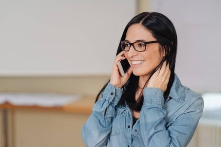 Young smiling long-haired woman wearing glasses talking on phone in office
