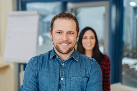 Handsome friendly young business manager or team leader posing smiling at the camera in front of a young female work colleague or team member