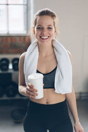 Happy smiling healthy young woman in a gym with a towel around her neck holding a disposable takeaway cup of beverage as she relaxes after a workout