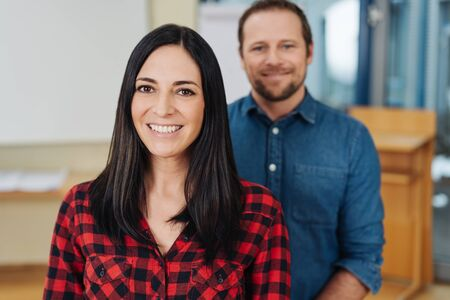 Confident successful young businesswoman posing in front of her male business partner in a modern office smiling at the camera
