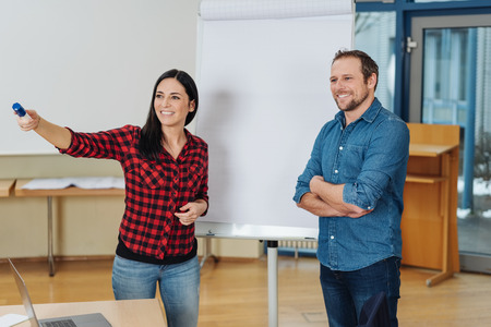 Happy successful young business team doing a presentation standing in front of a flip chart pointing to a conference table as they take questions or suggestions