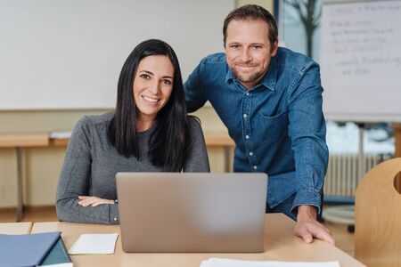 Successful motivated friendly business partners posing together behind a laptop computer in a modern spacious office smiling at the camera