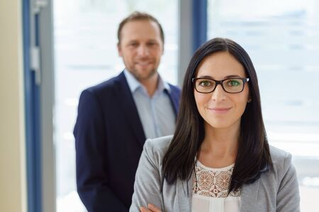 Smart friendly young business manageress wearing glasses posing with folded arms smiling at the camera in front of a male partner or colleague