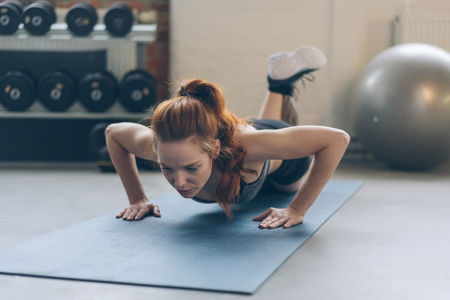 Fit young woman working out doing press ups on a yoga mat in a gym in a low angle view with gym equipment in the background
