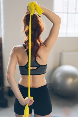 Young redhead woman suing exercise straps in a gym to stretch her muscles in a rear view with the strap behind her back Stock Photo