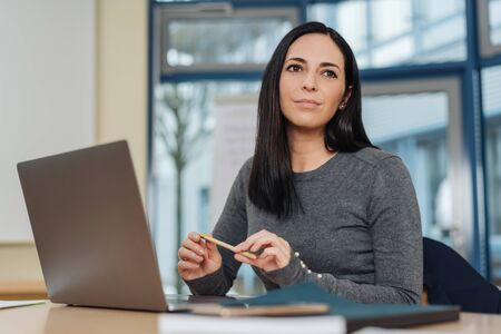 Thoughtful attractive young office worker sitting at her desk with a laptop looking aside with a pensive expression in a low angle view