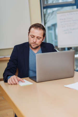 Thoughtful businessman working at his laptop sitting at an office table reading notes on a notepad alongside