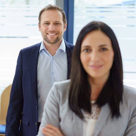 Portrait of cheerful businessman standing behind smiling woman