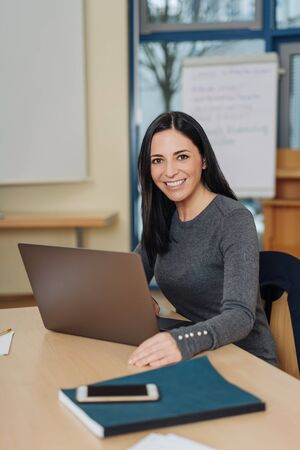 Portrait of young cheerful woman sitting in front of computer at office Stock Photo