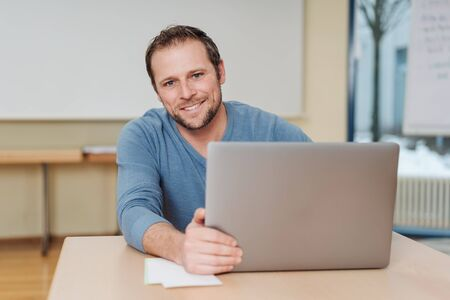 Portrait of smiling man sitting at desk in front of laptop Stock Photo