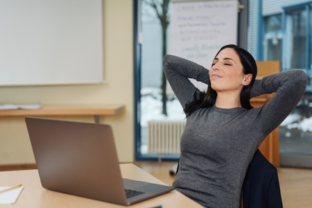 Young businesswoman taking a break to relax at her desk in the office sitting back with closed eyes and her hands behind her head