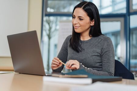 Attractive businesswoman smiling with pleasure as she reads information on her laptop computer in a low angle view in an office