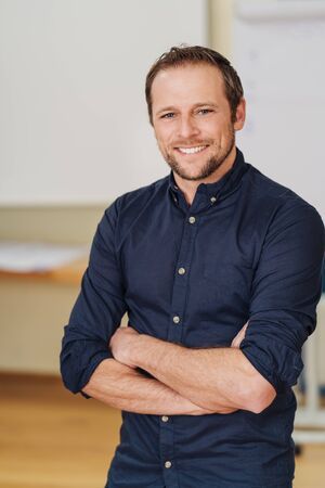 Confident relaxed businessman with folded arms and a friendly smile standing in an office looking at the camera