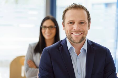Handsome young businessman with a lovely smile posing in a bright office looking at the camera with a female co-worker behind him