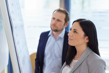 Young businesswoman standing reading a flip chart as she has a meeting with a male colleague, team member or partner in a close up profile view