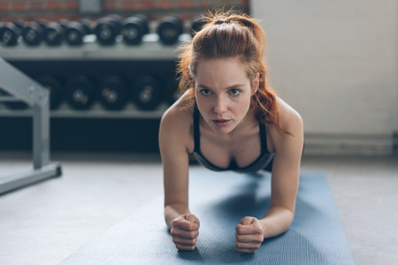 Young woman working out on a mat in a gym balancing on her forearms and tones to strengthen her muscles with a look of concentration