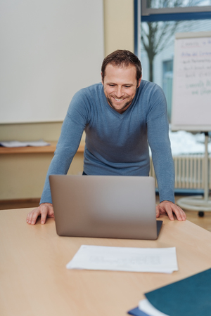 Happy successful young businessman leaning over an office table reading his laptop with a beaming smile of satisfaction