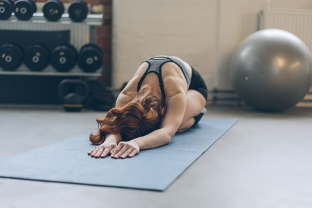 Young woman doing exercises on a mat in a gym bending forwards stretched out with a pilates ball and weights visible behind her