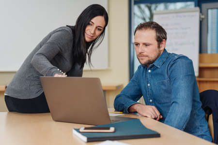 Two work colleagues, a man and woman, having a discussion pointing to information on a laptop screen as they sit together at an office table Stock Photo