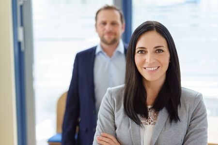 Portrait of smiling businesswoman with man standing in background