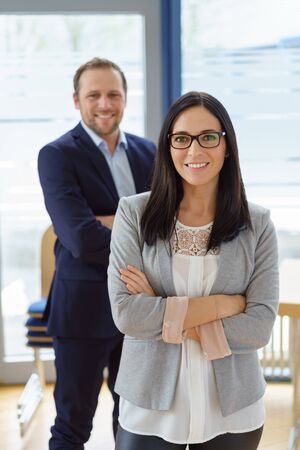 Confident successful business partnership with a smiling young woman with folded arms posing with her male colleague behind her in a modern spacious office