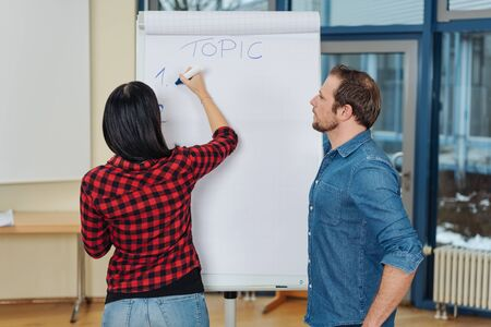 Young businesswoman and man doing a presentation working together on a flip chart writing notes in a large modern office Stock Photo
