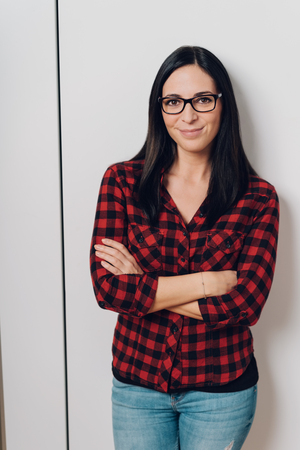 Confident attractive woman wearing glasses, denim jeans and a red plaid shirt standing with folded arms smiling at the camera against a white wall Stock Photo