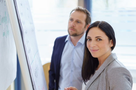 Attractive stylish female business executive standing in front of a flip chart with a male colleague turning to smile at the camera