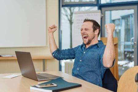 Excited jubilant businessman celebrating a success cheering and punching the air with his fists as he sits at a desk in an office Stock Photo