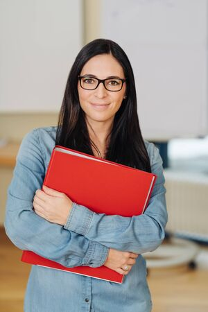 Portrait of smiling long-haired woman wearing glasses holding red ring binder