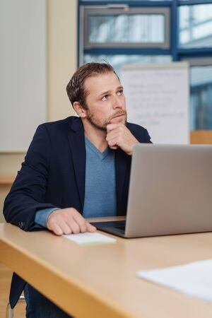 Businessman sitting at a desk deep in thought resting his chin on his and as he stares upwards with a pensive expression Stock Photo
