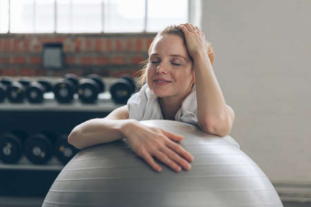 Young woman relaxing in a gym with a pilates ball after working out resting her arms on the top and closing her eyes with a smile