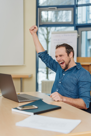 Jubilant businessman cheering a success and punching the air with his fist as he sits at his desk in front of a laptop