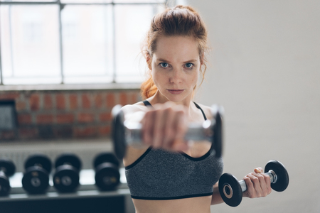Focused determined young woman lifting weights holding a dumbbell in her hand extended towards the camera with focus to her face Stock Photo