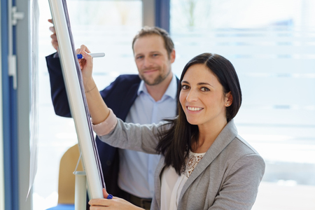 Stylish young businesswoman or manageress working with a flip chart turning to smile at the camera watched by a male colleague or partner