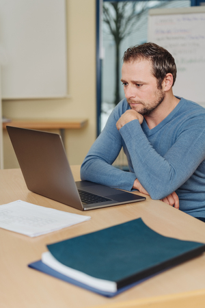Dedicated young businessman engrossed in his work sitting at a laptop computer in an office reading the screen Stock Photo
