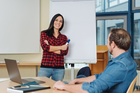 Relaxed confident young woman doing a business presentation in a conference room smiling as she talks to a young businessman