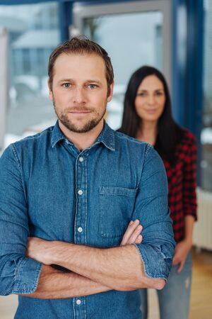 Serious confident businessman standing with folded arms in an office staring at the camera with a female colleague in the background