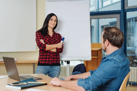 Two business partners brainstorming together in the office in front of a blank flip chart having a serious discussion, the man seated at a table and woman standing