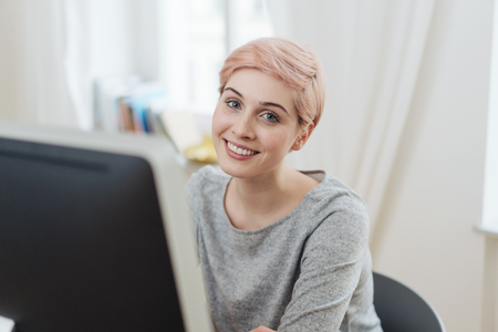 Beautiful young woman with short haircut sitting at computer and friendly smiling when looking at camera Reklamní fotografie