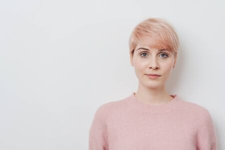 Serious attractive young strawberry blond woman with a short modern hairstyle staring at the camera over a white studio background with copy space Stock Photo - 97701940