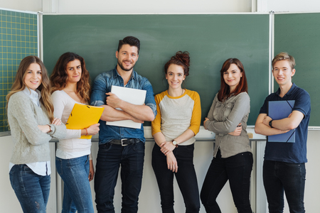 Diverse group of successful university students standing in a line in front of the chalkboards with class notes smiling at the camera