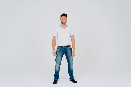 Attractive friendly handsome young man wearing faded old jeans and a white top standing with his arms relaxed at his sides grinning at the camera over a white studio background