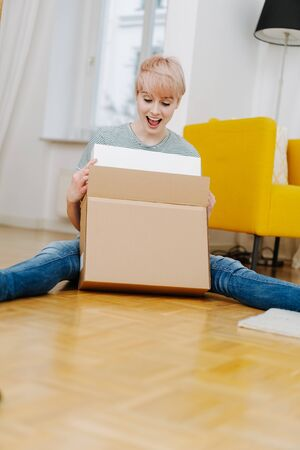 Vivacious excited woman opening a courier package as she sits on the wooden floor of her apartment with copy space in the foreground